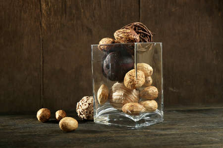 Composition of nuts and wooden balls in glass on resembling wood table