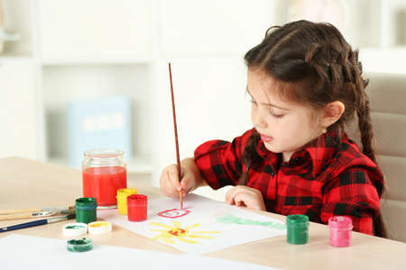 Cute little girl painting picture on home interior background Banco de Imagens - 95467112