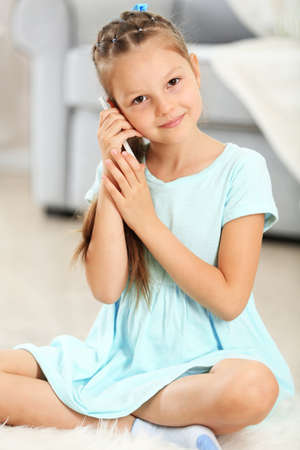 Little cute girl with mobile phone sitting on carpet, on home interior background