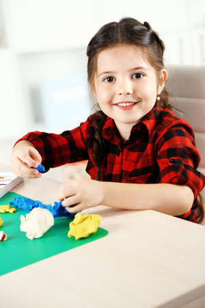 Cute little girl moulds from plasticine on table Stock Photo