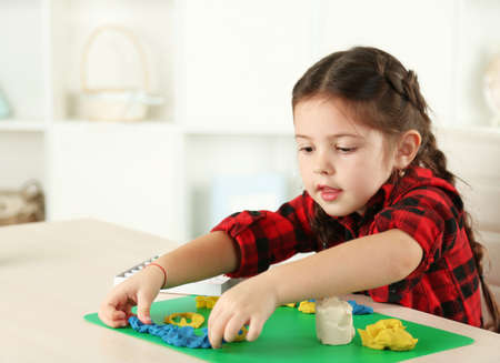 Cute little girl moulds from plasticine on table Reklamní fotografie