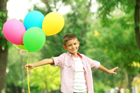 Little boy with balloons in the park Stock Photo