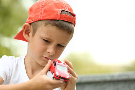 Little boy playing with toy car outside