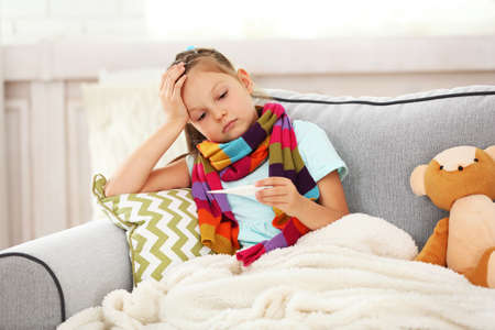 Sick girl with cold sitting on sofa