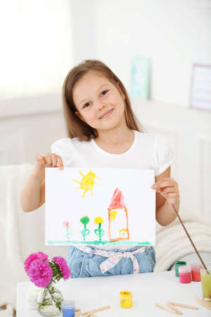 Cute little girl  with picture on home interior background Imagens