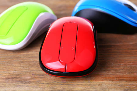 Colourful wireless computer mouses on wooden background Stock Photo