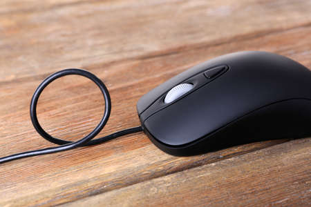 Computer mouse with cord on wooden background Stock Photo