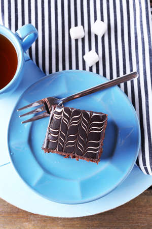 Sweet chocolate cake on blue plate with cup of tea on wooden table