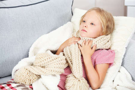 Little girl with sore throat lying on the bed Stock Photo