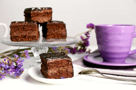 Served table with chocolate cakes and a cup of tea on white wooden background