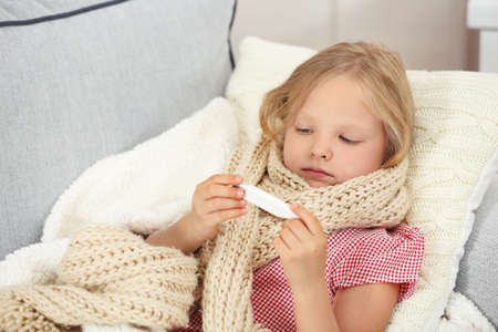 Little girl with sore throat checking temperature