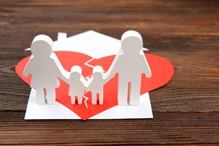 Paper cutout silhouette of a family split apart on a paper heart, divorce concept