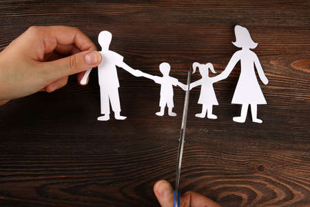 A hand cutting paper chain of a family, divorce and child custody battle