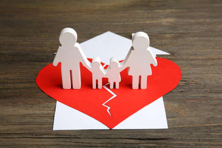 Cutout silhouette of a family split apart on a paper heart, divorce concept