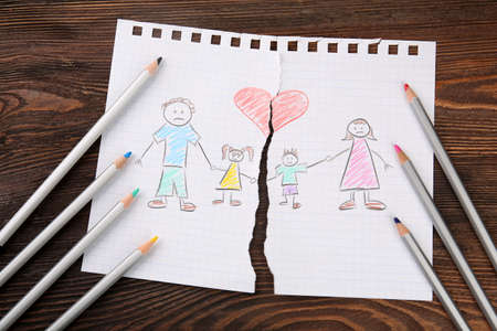Torn apart drawing of a family on wooden background 写真素材