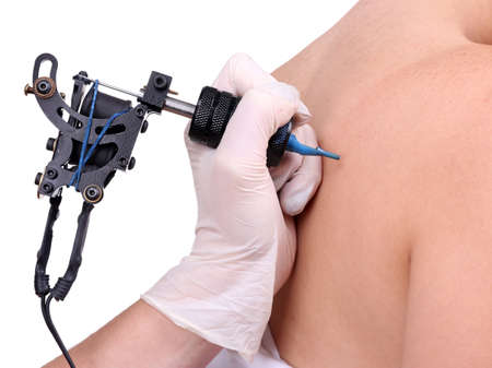 Tattooist draws on the womans right shoulder-blade on white background, close up