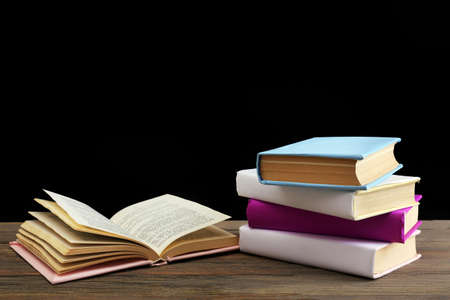 Pile of different books on wooden table against black background Stockfoto
