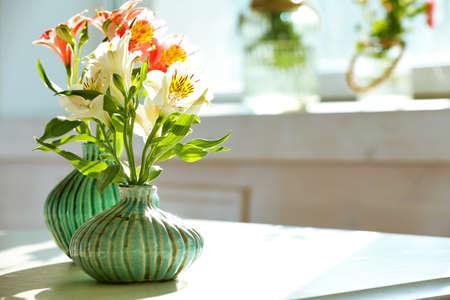 Beautiful Alstroemeria flowers in aquamarine vases on window background Stock Photo