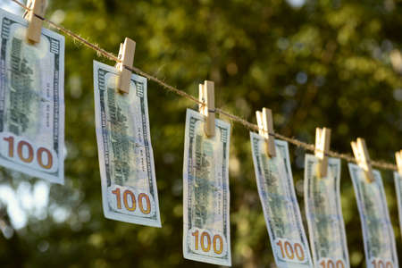 Concept of money laundering - one hundred bills hanging on a cord, outdoors Stock Photo