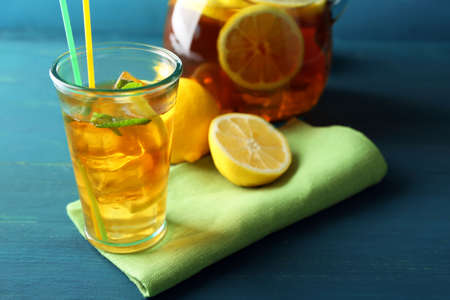 Iced tea with lemon on  color wooden background