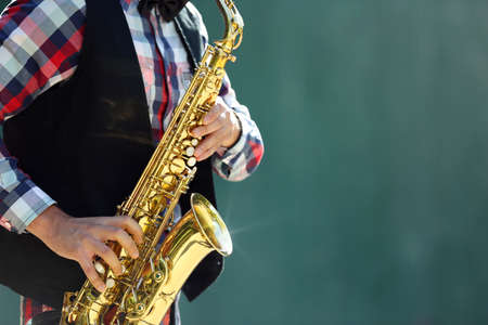 Young man playing on saxophone outside near the old wall Banco de Imagens