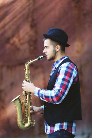Young man playing on saxophone outside near the old wall 写真素材