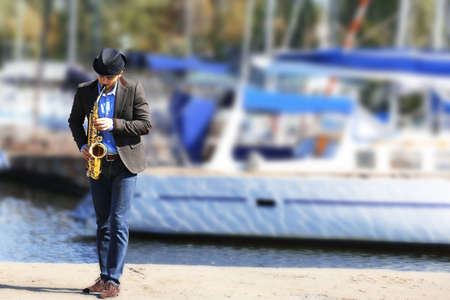 Handsome man plays sax in front of yacht Banque d'images