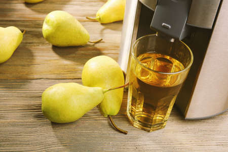 Stainless juice extractor with pears and glass of juice on wooden background, close up Stock Photo