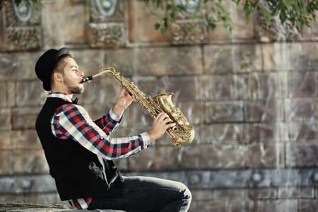 Handsome young man plays sax on stone wall background