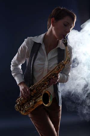 Attractive woman plays saxophone on dark blue background