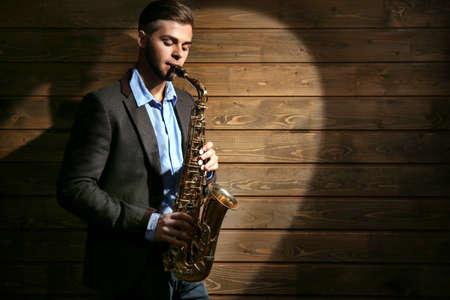 Elegant saxophonist plays jazz on wooden background