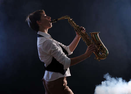 Attractive woman plays saxophone on dark background Foto de archivo