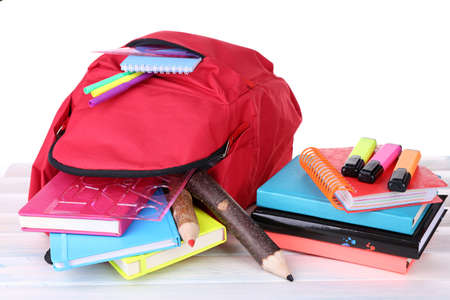 Red bag with school equipment on wooden table isolated on white Stock Photo