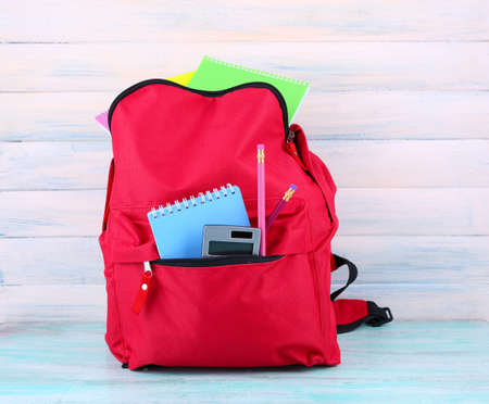 Red bag with school equipment on wooden background Stock Photo