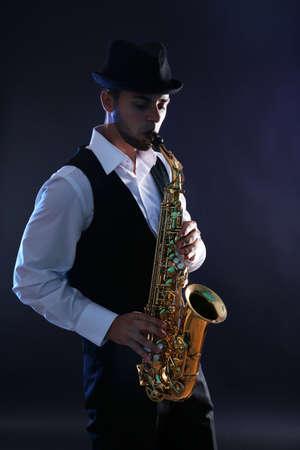 Elegant saxophonist plays jazz on dark background Foto de archivo