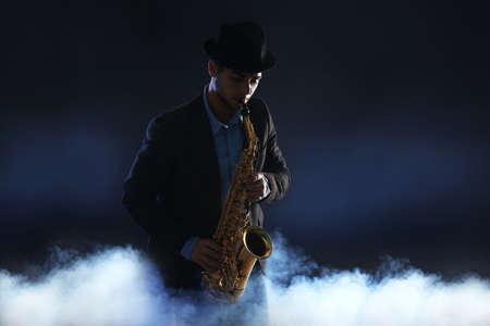 Elegant saxophonist plays jazz on dark background in a smoke Banque d'images