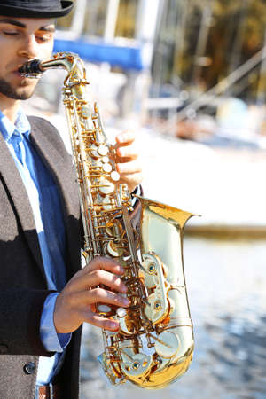 Saxophonist plays jazz outdoors, close up Banque d'images