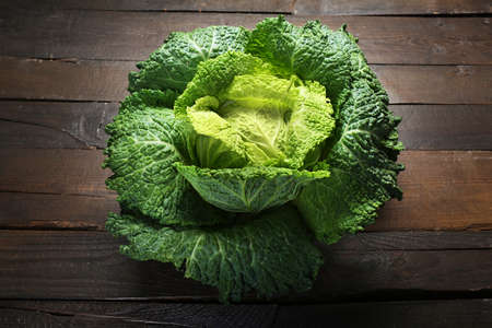 Savoy cabbage on wooden background Stock Photo