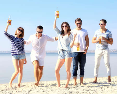 Young people with beer on the riverside Stock Photo