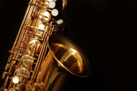 Beautiful golden saxophone on black background, close up Фото со стока