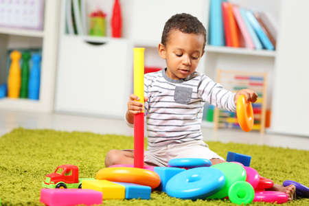 Little boy playing with his toys in the room Stock Photo