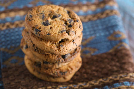 Cookies with chocolate crumbs on ornament napkin against blurred background, close up Stock Photo