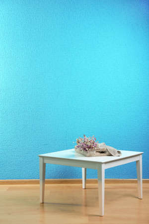 Little table with flowers on blue wall background