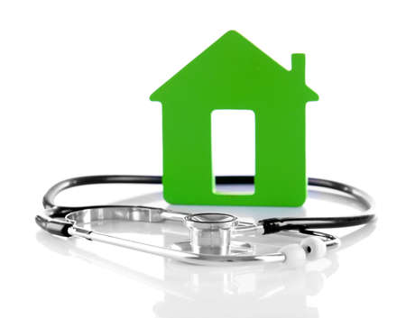 Concept of family medicine - green house and stethoscope isolated on white background Stock Photo