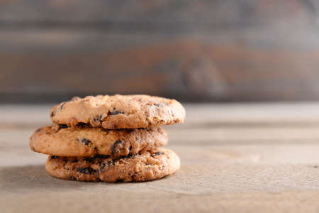 Cookies with chocolate crumbs on wooden background