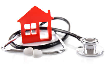 Concept of family medicine - red plastic house and stethoscope isolated on white background