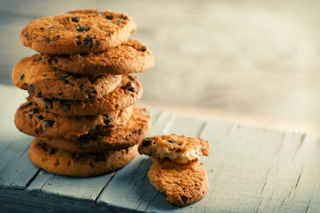 Cookies with chocolate crumbs on blue wooden table against blurred background, close up Stock Photo