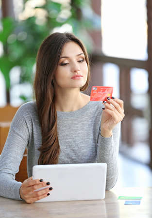Young woman trying to use bank card for paying bills online Stock Photo