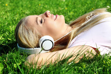 Young woman in earphones on grass