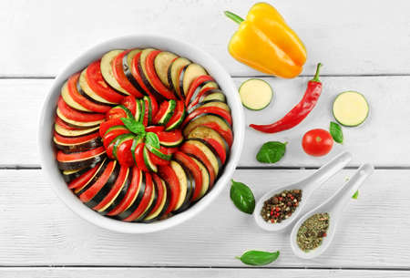 Ratatouille, stewed vegetable dish with tomatoes, zucchini, eggplant before cooking in pan, on wooden background